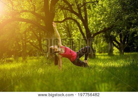 Morning yoga. Female doing yoga asana side plank pose with bent leg. Woman practicing Vasisthasana with bent leg. Toned image.