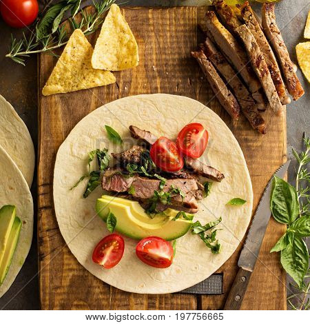 Making tacos with grilled steak, avocado and tomatoes, mexican food concept, overhead shot