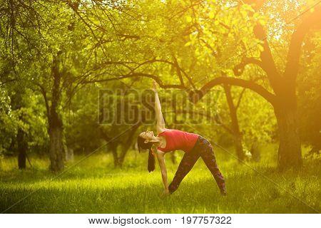 Girl doing yoga asana extended triangle. Yoga practicing outdoors, woman standing in Utthita Trikonasana. Toned image.