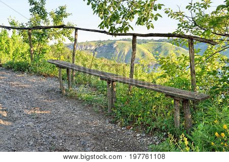 Wooden Bench In The Background Of A Valley