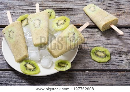 Homemade kiwi popsicle withe ice on wooden background