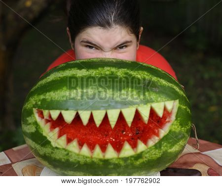 teenager girl perform moster with water melon cut sharp teeth mouth close up photo
