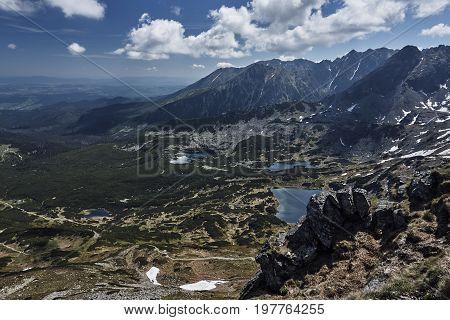 Peak rock snow meadow forest peak spruce tree shrub sky cloud rock plant landscape back lake water mountains Tatra Mountains Poland Europe