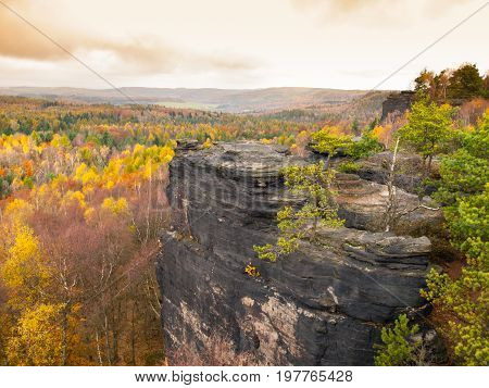 Sandstone rock formation in the middle of colorful autumn forest. Dramatic evening view. Tisa Rocks, aka Tiske Walls, Czech-Saxon Switzerland, Czech Republic
