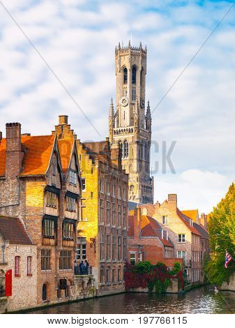 Belfry Tower and brick houses at water canal, Bruges, Belgium. HDR image.