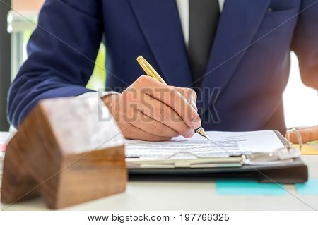 Concept home purchase contract,Businessmen are signing a house purchase contract,The concept of selling a home is signing a contract.