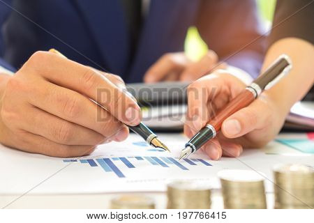 Male and female office workers analyze data graphs,Male and female office workers use a pen in their hands pointing at the graph.
