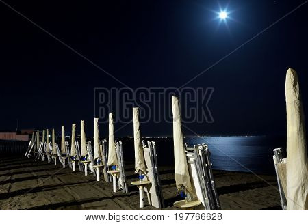 Empty beach at night with full moon reflecting in the sea Marina di San Nicola Lazio Italy.