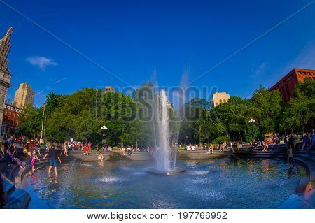 NEW YORK - JULY 22, 2017: Unidentified people enjoying the summer day in the Washington Square Park, inside of the fountain, with a small rainbow in the middle of the fountain in New York, Usa, fish eye effect.