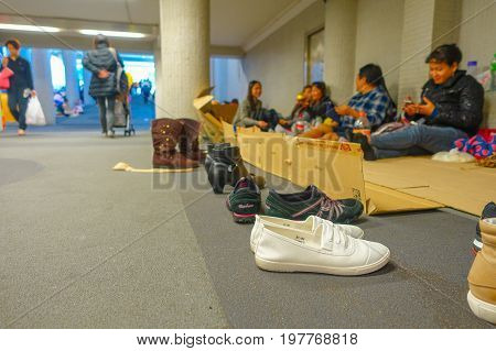 HONG KONG, CHINA - JANUARY 26, 2017: Close up of nannies shoes, with unidentified foreign nannies on day off resting in downtown Hong Kong.