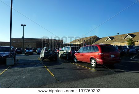 JOLIET, ILLINOIS / UNITED STATES - DECEMBER 4, 2015: Automobiles are parked in the parking lot of the Drauden Point Middle School.