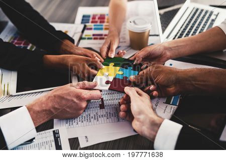 Businessmen working together to build a colored puzzle. Concept of teamwork, partnership, integration and startup.