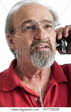 Elder man with COPD talking on the phone while wearing an oxygen cannula for supplemental air.