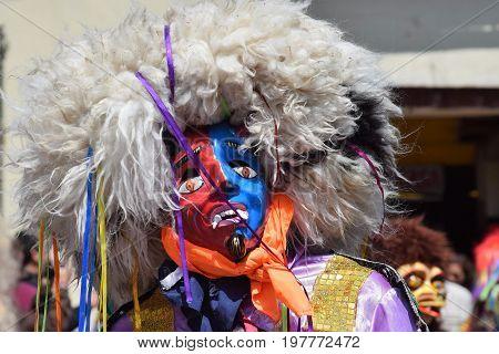 Reveler in street festival wearing colorful mask in Cuzco, Peru