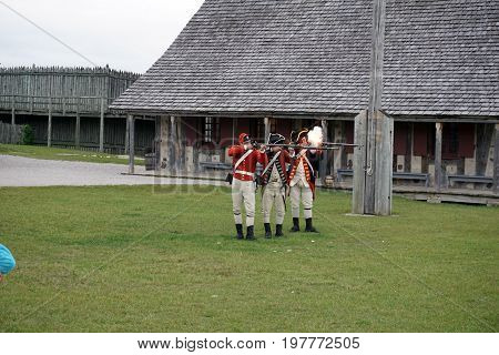 MACKINAW CITY, MICHIGAN / UNITED STATES - JUNE 18, 2017: Costumed interpreters, on the parade ground of Fort Michilimackinac, in the Colonial Michilimackinac State Park, demonstrate the firing of muskets.