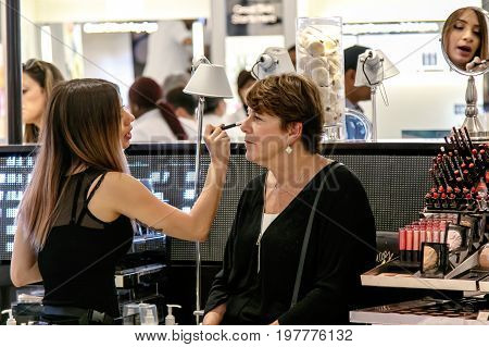 New York July 27 2017: Beauty section employee is applying cosmetics to a female customer on the floor of Macy's department store. The employee's face is reflected in the mirror behind the customer.