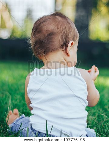Little girl in white outfit sitting in grass in park looking away from camera
