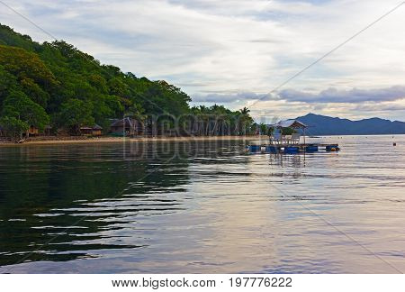 Beach on a small island with floating gazebo in sea waters. Quiet sea at dawn on a tropical beach in Philippines.