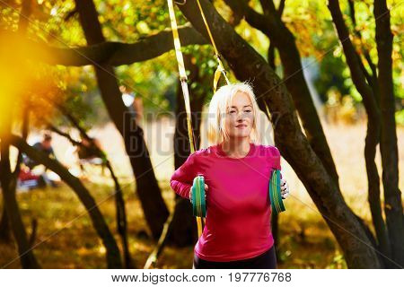 Young woman doing suspension training with fitness straps on fresh air