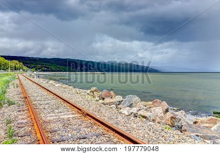 Railroad With Stormy Sky And Saint Lawrence River In Saint-irenee, Quebec, Canada In Charlevoix Regi