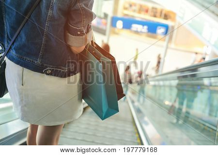 Female standing on escalator spending customer consumerism at department store.