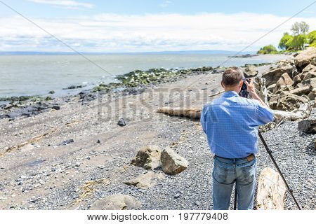 Photographer taking pictures of rocks and Saint Lawrence river in Saint-Irenee Quebec Canada in Charlevoix region with beach