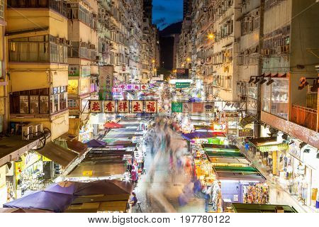 HONG KONG, JULY 11, 2017: Night market in busy Fa Yuen Street in Mong Kok Hong Kong China. The area is popular with tourists and locals for its cheap food and fashion clothing. Long exposure for crowd motion effect.