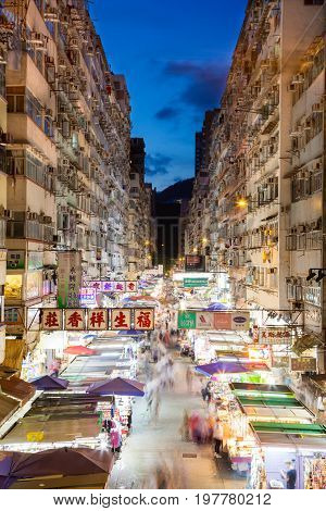 HONG KONG, JULY 11, 2017: Night market in busy Fa Yuen Street in Mong Kok Hong Kong China. The area is popular with tourists and locals for its cheap food and fashion clothing. Long exposure for crowd motion effect. Vertical orientation.