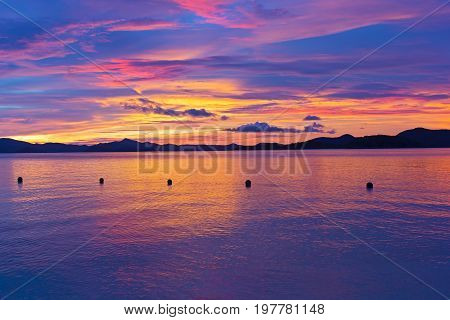 Unearthly sunset colors on a tropical island. Ocean landscape with mountain ridges on the horizon at sunset.