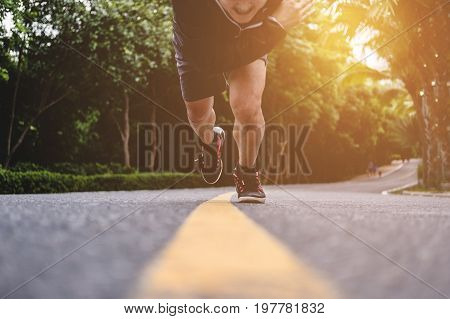 Runner running straight to camera, on the road, selective focus on shoes
