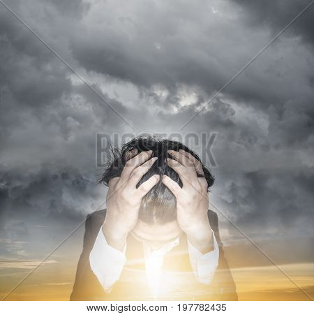 Stressed businessman with dark cloud and double exposure sunrise sky, hope and business problems concept