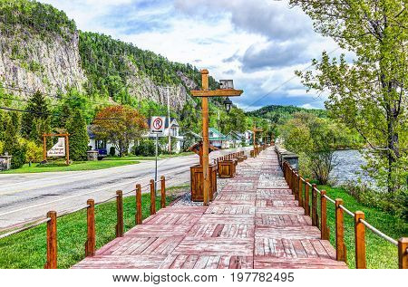 Petit-Saguenay Canada - June 2 2017: Wooden boardwalk terrace sidewalk painted red by river in Quebec village