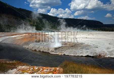 Cliff Geyser next to Iron Spring Creek in Black Sand Geyser Basin in Yellowstone National Park in Wyoming USA