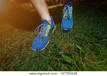 Jogging on green grass background close-up. Blue colorful run shoes