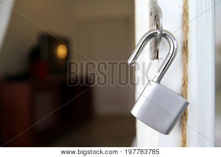unlocked padlock with chain at blue wooden door