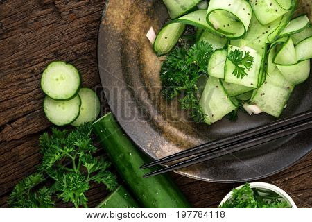 Close up cucumber salad and with chia seeds and green parsley leaf in black plate heathy salad for anti aging with rich of antioxidant organic food concept