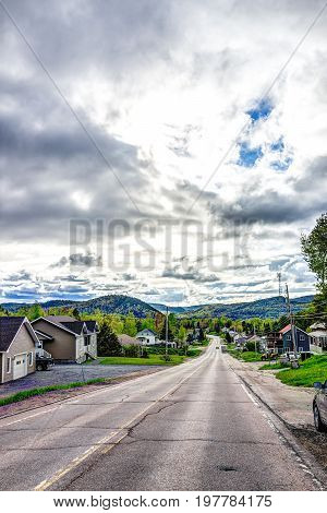 L'Anse-Saint-Jean Canada - June 2 2017: Houses cityscape and highway road in Quebec village by Saguenay fjord river with stormy sky