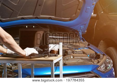 Mechanic checking modern car with laptop computer diagnostic. Auto computer diagnostic