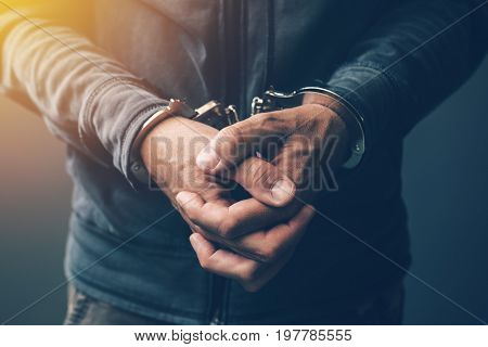 Arrested computer hacker and cyber criminal with handcuffs close up of hands
