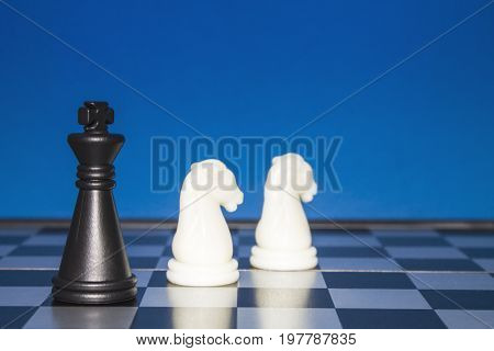 Chess As A Business. A Black Figure Controls Two White Horses.