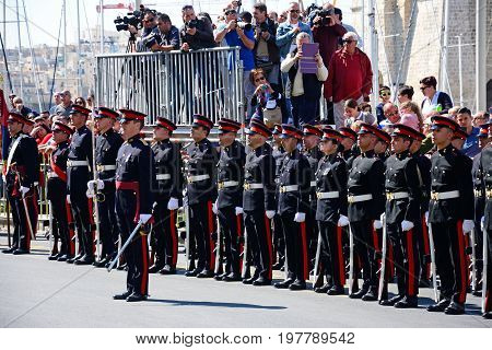 VITTORIOSA, MALTA - MARCH 31, 2017 - Freedom day celebrations with military personnel standing in a line by the Freedom Day monument and paparazzi to the rear Vittoriosa Malta Europe, March 31, 2017.