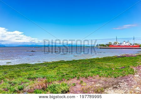 L'islet, Canada - June 4, 2017: Saint Lawrence River Beach Shore With View Of Red Ship And Canadian