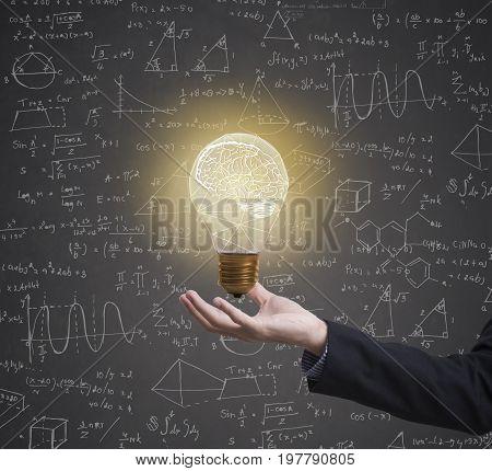 lightbulb brainstorming creative idea math formula on business hand.