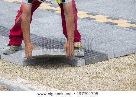 Mason Hands Laying Paver Bricks