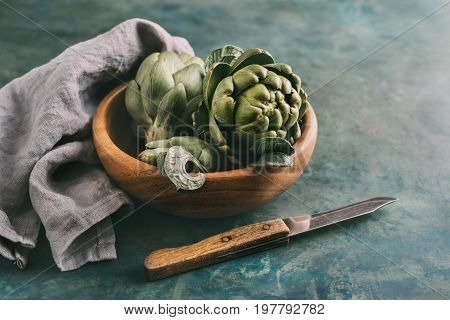 Ripe organic artichokes in a wooden bowl with napkin and knife. Selective focus. Toned image.