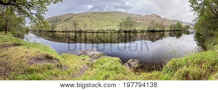 Trees reflecting on the river Orchy, Glen Orchy, Scotland, United Kingdom