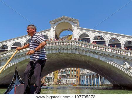 Venice Italy - June 20 2017: Unidentified Gondolier in front of the Rialto bridge in Venice Italy. Venice Grand Canal.