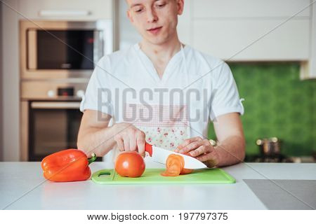 man cuts vegetables together in the kitchen.