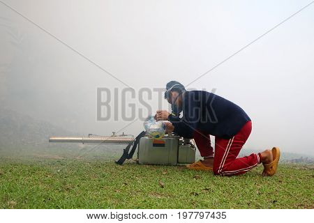 Worker with Smoke and Fogging Machine in the garden Samui island Thailand July 10 2017