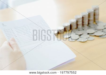 Woman hold passbook on hand coins background